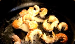 обжаривают раздавленную чесночную дольку и добавляем мясо раков