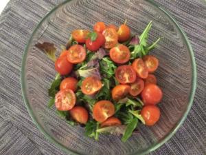 Нарезаем черри и добавляем к листьям салата